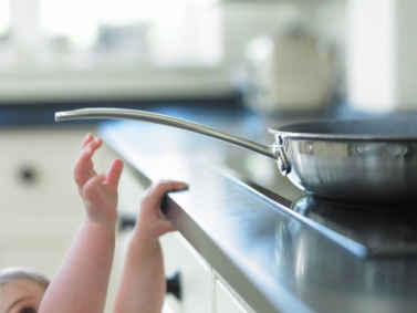 Baby reaching for hot frying pan on stove